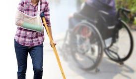 Τραυματισμένη γυναίκα που στέκεται πράσινο που πετιέται με στο βραχίονα και τη σφεντόνα βραχιόνων usin Στοκ Εικόνες