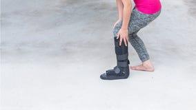 τραυματισμένη γυναίκα που φορά sportswear με το μαύρο στήριγμα αστραγάλων στο πόδι s Στοκ φωτογραφία με δικαίωμα ελεύθερης χρήσης