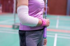 τραυματισμένη γυναίκα που φορά sportswear τον επίπονους βραχίονα και το πόδι με το gauz Στοκ Φωτογραφία