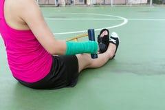 Τραυματισμένη γυναίκα που φορά sportswear τον επίπονο βραχίονα με τον επίδεσμο γάζας Στοκ Εικόνα
