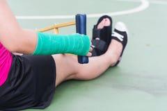 Τραυματισμένη γυναίκα που φορά sportswear τον επίπονο βραχίονα με τον επίδεσμο γάζας Στοκ Φωτογραφίες
