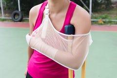 Τραυματισμένη γυναίκα που φορά sportswear τον επίπονο βραχίονα με τον επίδεσμο γάζας, Στοκ Εικόνες