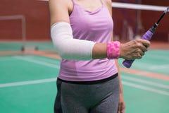 Τραυματισμένη γυναίκα που φορά sportswear τον επίπονο βραχίονα με τον επίδεσμο γάζας Στοκ Φωτογραφία