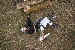 Τραυματισμένος υλοτόμος με το αλυσιδοπρίονο που βρίσκεται στο έδαφος μετά από την πτώση Στοκ φωτογραφίες με δικαίωμα ελεύθερης χρήσης