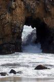 Τραχιά ακτή Καλιφόρνιας με το Ειρηνικό Ωκεανό που συντρίβει μέσω του ανοίγματος στους βράχους στοκ εικόνα