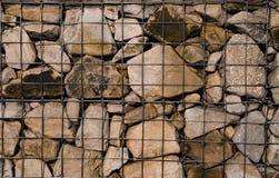 Τραχύ τυποποιημένο της υφής έμβλημα τέχνης με το διάστημα για το κείμενο Το πλέγμα μετάλλων κρατά πολλές πέτρες στοκ φωτογραφίες