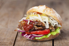Τργμένο χοιρινό κρέας σε ένα κουλούρι Στοκ Φωτογραφίες