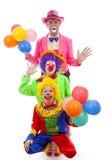 Τρεις άνθρωποι έντυσαν επάνω ως ζωηρόχρωμοι αστείοι κλόουν Στοκ εικόνα με δικαίωμα ελεύθερης χρήσης