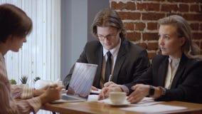 Τρεις άνθρωποι απασχολούνται μαζί και συζητούν σε μια σύμβαση σε έναν καφέ Οι γυναίκες και ο άνδρας σε ένα εστιατόριο ή έναν καφέ απόθεμα βίντεο