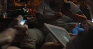Τρεις άνθρωποι που χρησιμοποιούν τα τηλέφωνα και την ταμπλέτα τους στον καφέ απόθεμα βίντεο