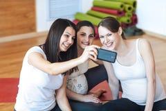 Τρεις έγκυοι γυναίκες που χαμογελούν και που φωτογραφίζονται με κινητό τηλέφωνο στοκ εικόνες