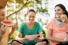 Τρεις έγκυοι γυναίκες στηρίζονται στη φύση μετά από να κάνουν τη γιόγκα Ένας από τους κρατά μια ταμπλέτα Στοκ φωτογραφία με δικαίωμα ελεύθερης χρήσης