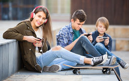Τρεις έφηβοι με τα τηλέφωνα υπαίθρια Στοκ φωτογραφία με δικαίωμα ελεύθερης χρήσης