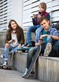 Τρεις έφηβοι με τα τηλέφωνα υπαίθρια Στοκ Εικόνες
