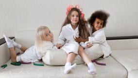 Τρεις αδελφές αγκαλιάζουν τη συνεδρίαση στον καναπέ στοκ εικόνα