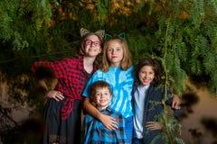 Τρεις αδελφές και ο αδελφός τους κάτω από μια χαμηλή τοποθέτηση δέντρων ένωσης στοκ εικόνες