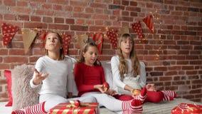 Τρεις αδελφές που κάθονται στο κρεβάτι στις μαλακές πυτζάμες και που παίζουν με τα κόκκινα μήλα Η κρεβατοκάμαρα είναι διακοσμημέν απόθεμα βίντεο