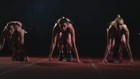 Τρεις αθλητές αθλητικών κοριτσιών τη νύχτα στη treadmill έναρξη για τον αγώνα στην απόσταση ορμής από τη θέση συνεδρίασης φιλμ μικρού μήκους
