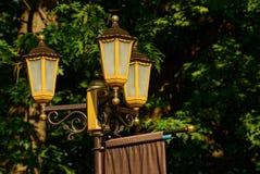 Τρεις λαμπτήρες οδών σε έναν πόλο στο πάρκο Στοκ Φωτογραφία
