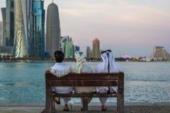 Τρεις αραβικοί άνθρωποι που κάθονται σε έναν πάγκο στη θέση πυρήνων Doha και που εξετάζουν τον κόλπο στοκ εικόνα