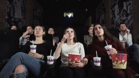 Τρεις αρκετά θηλυκοί φίλοι προσέχουν έναν τρομακτικό κινηματογράφο Η μέση γυναίκα αντιδρά με τον κλονισμό απόθεμα βίντεο