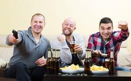 Τρεις αρσενικοί φίλοι που κάθονται στον πίνακα με την μπύρα Στοκ φωτογραφία με δικαίωμα ελεύθερης χρήσης