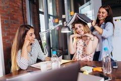 Τρεις αστείοι νέοι σπουδαστές που έχουν τη διασκέδαση καθμένος στο γραφείο που προετοιμάζεται για το διαγωνισμό στο δωμάτιο μελέτ στοκ εικόνες