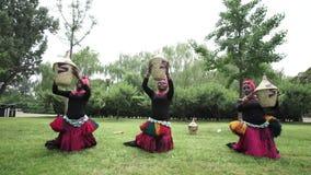 Τρεις αφρικανικές γυναίκες είναι χορεύοντας ένας λαϊκός χορός στα παραδοσιακά κοστούμια με τα ψάθινα καλάθια απόθεμα βίντεο