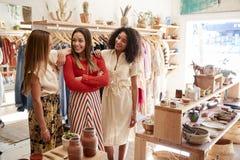 Τρεις βοηθοί πωλήσεων θηλυκών που εργάζονται στο κατάστημα ιματισμού και δώρων στοκ εικόνες