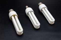 Τρεις βολβοί εξοικονόμησης ενέργειας που βρίσκονται σε έναν μαύρο πίνακα στοκ εικόνα