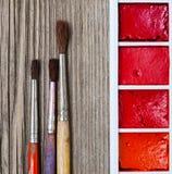 Τρεις βούρτσες για τη ζωγραφική και ένα κουτί χρωμάτων Στοκ Εικόνες