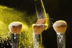 Τρεις βούρτσες για το makeup με την κίτρινη σύνθεση κονιοποιούν στην κίνηση σε ένα μαύρο υπόβαθρο στοκ φωτογραφία
