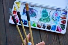 Τρεις βούρτσες σε ένα χέρι και ένα σύνολο χρωμάτων σε ένα κιβώτιο σε έναν πίνακα Στοκ Φωτογραφία