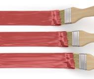 Τρεις βούρτσες χρωμάτων με τα κόκκινα κτυπήματα χρωμάτων Στοκ Φωτογραφία