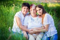 Τρεις γενεές των γυναικών - η γιαγιά, μητέρα και η κόρη Ένα οικογενειακό πορτρέτο στα πράσινα υπαίθρια στοκ εικόνες με δικαίωμα ελεύθερης χρήσης