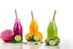 Τρεις γεύσεις του χυμού φρούτων στα μπουκάλια με ένα άχυρο στο άσπρο β Στοκ Φωτογραφία