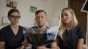 Τρεις γιατροί της οδοντιατρικής μελετούν την ακτίνα X ένας από τους ασθενείς τους Ακτίνα X των δοντιών απόθεμα βίντεο