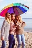 Τρεις γυναίκες κάτω από τη ζωηρόχρωμη ομπρέλα στοκ εικόνες