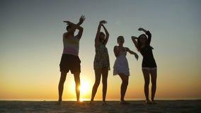 Τρεις γυναίκες και ένας άνδρας που χορεύει σε μια παραλία στο λυκόφως απόθεμα βίντεο