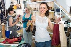 Τρεις γυναίκες που επιλέγουν τα παπούτσια στο κατάστημα Στοκ Εικόνες