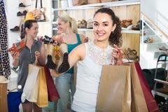 Τρεις γυναίκες που επιλέγουν τα παπούτσια στο κατάστημα Στοκ Φωτογραφίες