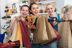 Τρεις γυναίκες που επιλέγουν τα παπούτσια στο κατάστημα Στοκ εικόνες με δικαίωμα ελεύθερης χρήσης