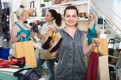 Τρεις γυναίκες που επιλέγουν τα παπούτσια στο κατάστημα Στοκ εικόνα με δικαίωμα ελεύθερης χρήσης