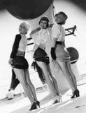 Τρεις γυναίκες που κοιτάζουν πέρα από τους ώμους τους και που παρουσιάζουν πόδια τους (όλα τα πρόσωπα που απεικονίζονται δεν ζουν στοκ φωτογραφία