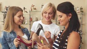 Τρεις γυναίκες που συζητούν τα παπούτσια στο κατάστημα παπουτσιών απόθεμα βίντεο