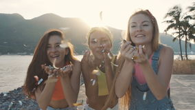 Τρεις γυναίκες φίλων που φυσούν έναν ψεκασμό του κομφετί στην παραλία στο ηλιοβασίλεμα απόθεμα βίντεο
