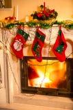 Τρεις γυναικείες κάλτσες Χριστουγέννων που κρεμούν στη διακοσμημένη εστία Στοκ Φωτογραφία