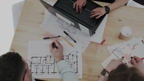 Τοπ υπερυψωμένη άποψη Τρεις δημιουργικοί επαγγελματίες σχεδίου που εργάζονται έντονα με το πρόγραμμα κτηρίου Σχεδιάγραμμα, αρσενι απόθεμα βίντεο