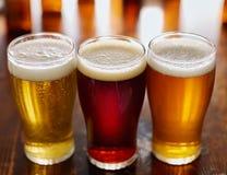 Τρεις διαφορετικοί τύποι μπυρών στις κούπες γυαλιού στοκ φωτογραφίες