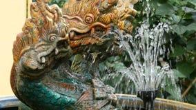 Τρεις-διευθυνμένος πράσινος δράκος ως παραδοσιακό βουδιστικό σύμβολο Άγαλμα και μια πηγή του δράκου στον κήπο της Ταϊλάνδης απόθεμα βίντεο